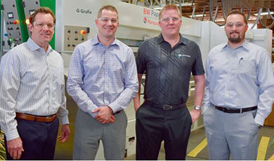 From left, Dean DeGroot, John Kula, Jeff Kula and Andrew DeGroot in front of the new G-Grafix rotary diecutter.